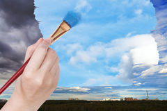 Paintbrush paints blue sky on rainy clouds Stock Image