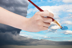 Paintbrush paints blue sky on storm clouds Stock Photography