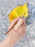 Paintbrush paints fallen leaf in yellow colour Stock Image