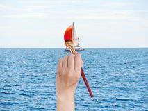 Paintbrush paints red sail of yacht Royalty Free Stock Photo