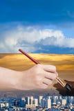 Paintbrush paints smog sky over blue city Stock Photo
