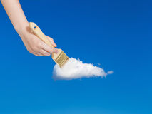 Paintbrush paints solitary white cloud in blue sky Royalty Free Stock Photography