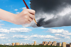 Paintbrush paints storm clouds over sunny city Royalty Free Stock Images