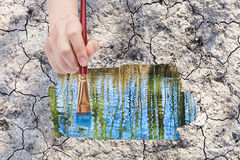 Paintbrush paints water puddle on dried earth Stock Images
