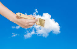 Paintbrush paints white cloud in blue summer sky Royalty Free Stock Images