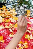 Paintbrush paints yellow autumn leaves on red car Royalty Free Stock Photography