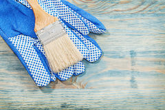 Paintbrush pair of protective gloves on wooden board constructio Stock Images
