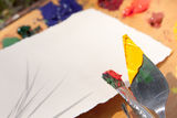 Paintbrush and palette knife with a piece of paper Stock Images
