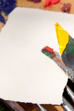 Paintbrush and palette knife with a piece of paper Royalty Free Stock Photo