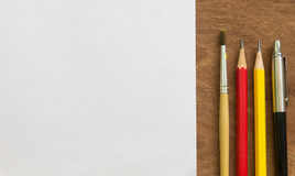 Paintbrush,pencil,pen with white paper on wooden table , creative concept.  Stock Photo