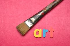A paintbrush with the word art. A paintbrush on a pink background with the word art royalty free stock photo