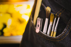 Paintbrush in the pocket of jeans with blurred picture background.  royalty free stock image