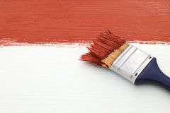 Paintbrush with red paint, painting over white board Stock Photo