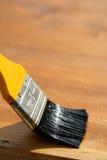 Paintbrush sliding over wooden surface, protecting wood Stock Image