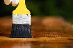 Paintbrush sliding over wooden surface, protecting wood Stock Photo