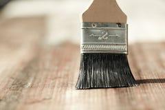 Paintbrush sliding over wooden surface, protecting wood Royalty Free Stock Photo