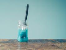 Paintbrush soaking in jar Royalty Free Stock Images