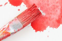 Paintbrush and splatter of red watercolor Stock Photos