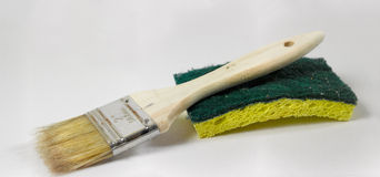 Paintbrush and sponge. Paint brush with a wooden handle resting on a household sponge Royalty Free Stock Image