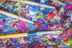 Paintbrush on tray with colorful paint spot on the surface Stock Photography