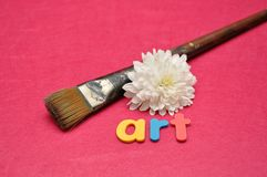 A paintbrush and a white aster with the word art. A paintbrush and a white aster on a pink background with the word art royalty free stock image
