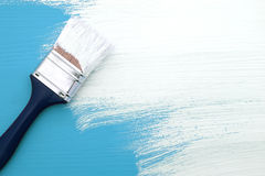 Paintbrush with white paint painting over blue Royalty Free Stock Photography