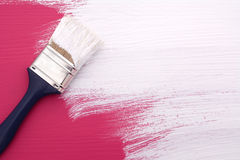 Paintbrush with white paint painting over pink Stock Photos