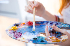Paintbrush in woman hands mixing paints on palette Royalty Free Stock Photography