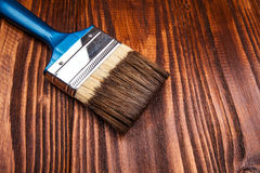 Paintbrush on wooden surface. Varnishing a wooden shelf using paintbrush Stock Photo