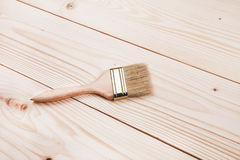 Paintbrush on wooden surface. Varnishing a wooden shelf using paintbrush Stock Images