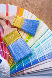 2 paintbrushes на цветовой палитре и деревянной доске Стоковые Фото