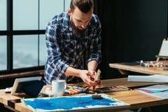 Paintbrushes студии работы художника бородатые фокусируют идею стоковое фото