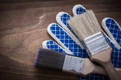 2 paintbrushes с деревянными ручками на перчатках безопасности работая Стоковые Фото