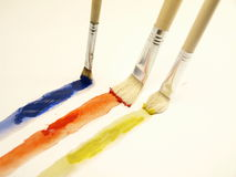 Paintbrushes. Three paintbrushes painting red, blue and yellow Stock Photos
