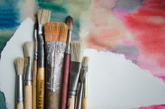 Paintbrushes on abstract colorful watercolor background with place for text. Blank for motivating quote, note, message. Stock Image