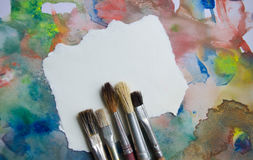 Paintbrushes on abstract colorful watercolor background with place for text. Blank for motivating quote, note, message. Royalty Free Stock Photos