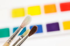 Paintbrushes against paints. Paintbrushes against various aquarelle paints stock images