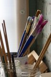 Paintbrushes in a Can in Front of a Window royalty free stock images