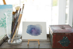 Paintbrushes, canvas and box on table Royalty Free Stock Photos