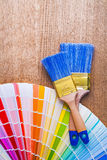 Paintbrushes and color  palette on brown wooden Royalty Free Stock Photos