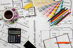 Paintbrushes and colorful paint samples on house plan  with pencil, notebook, tea Stock Photography