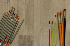 Paintbrushes of different sizes and multicolored pencils on grey wooden background as drawing concept. Art and creation background Royalty Free Stock Photography