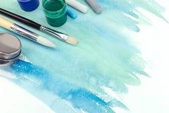 Paintbrushes, farby i pastel, piszą kredą na zielonej błękitnej akwareli Zdjęcia Stock