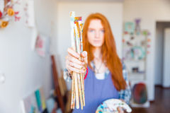 Paintbrushes holded by young redhead woman painter in artist workshop Stock Photography
