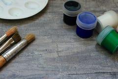 Paintbrushes i stubarwna akwarela malują jako rysunkowy pojęcie i paleta na popielatym kamiennym tle Fotografia Royalty Free