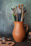 Paintbrushes in a jug from potters clay, palette and paint tubes Stock Photos