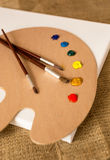 Paintbrushes lying on wooden pallet with oil paint blobs Stock Photo