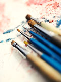Paintbrushes on oil painting canvas, vertical composition Royalty Free Stock Photo