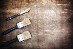 Paintbrushes on an old wooden table, space for text Royalty Free Stock Image