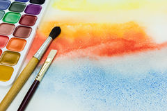 Paintbrushes and palette of aquarelle paints on watercolor background. Artist paintbrushes and palette of aquarelle paints on watercolor painting background stock images